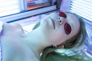 Woman With Sunglasses On Tanning Bed In Solarium