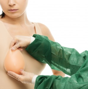 Plastic surgeon woman trying on silicon breast implant on client