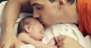 Father kissing his baby boy forehead while his sleeping and holding hands. Parent love.